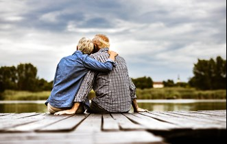 Two people sitting on a pier hugging